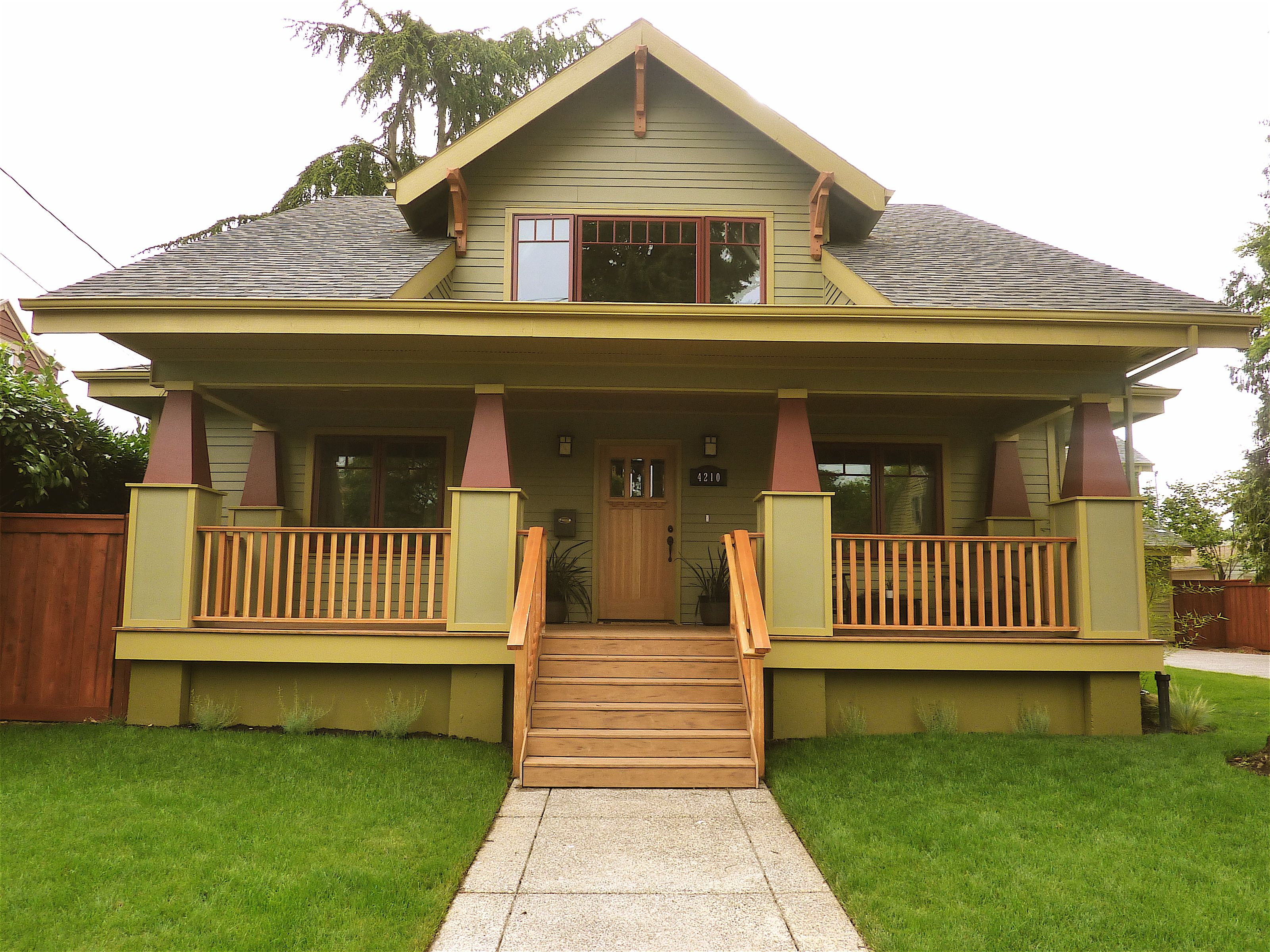 Green and burgundy wood detailed craftsman bungalow for Craftsman home builders