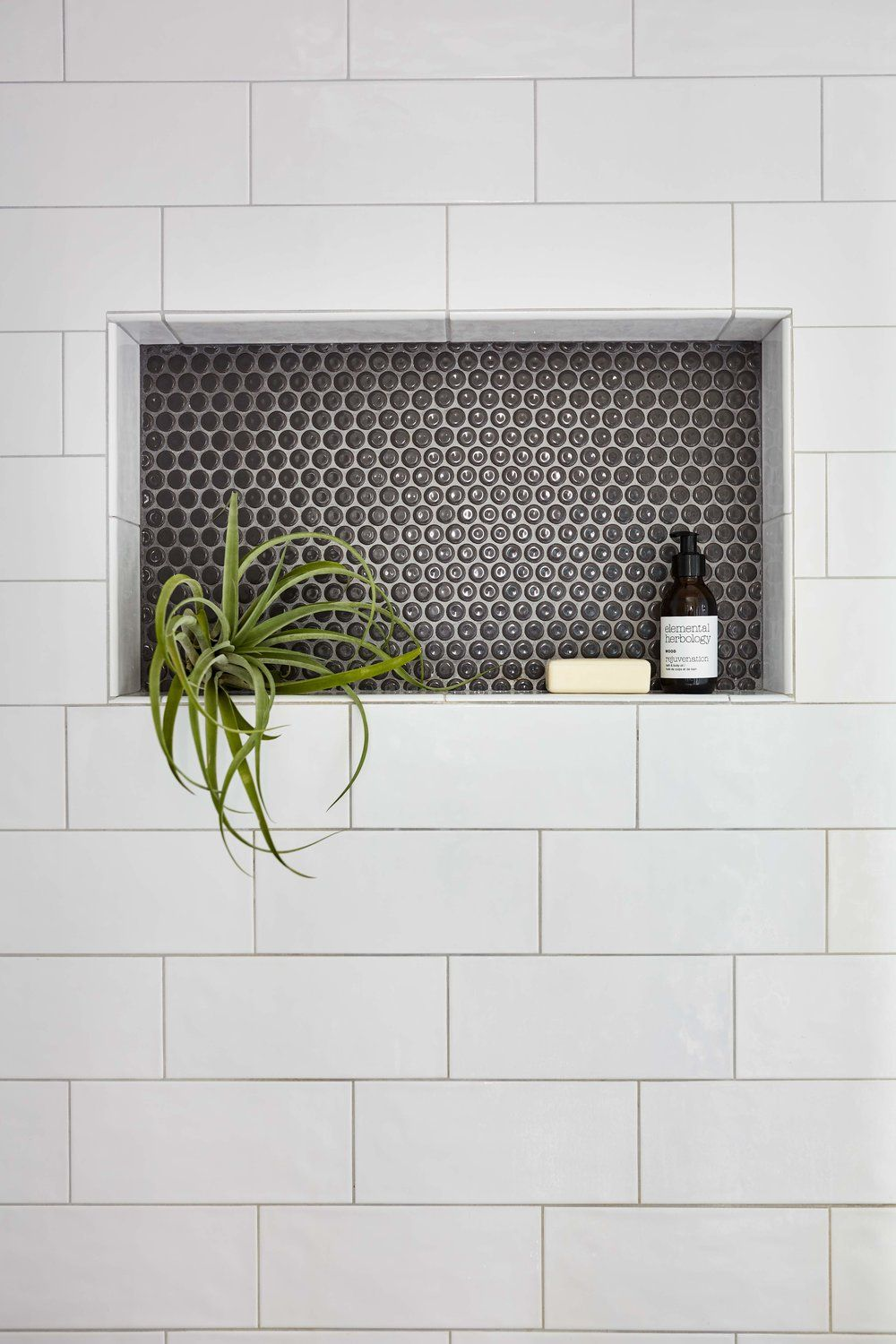 Shower niche with large subway tile and penny tile. #showertiles
