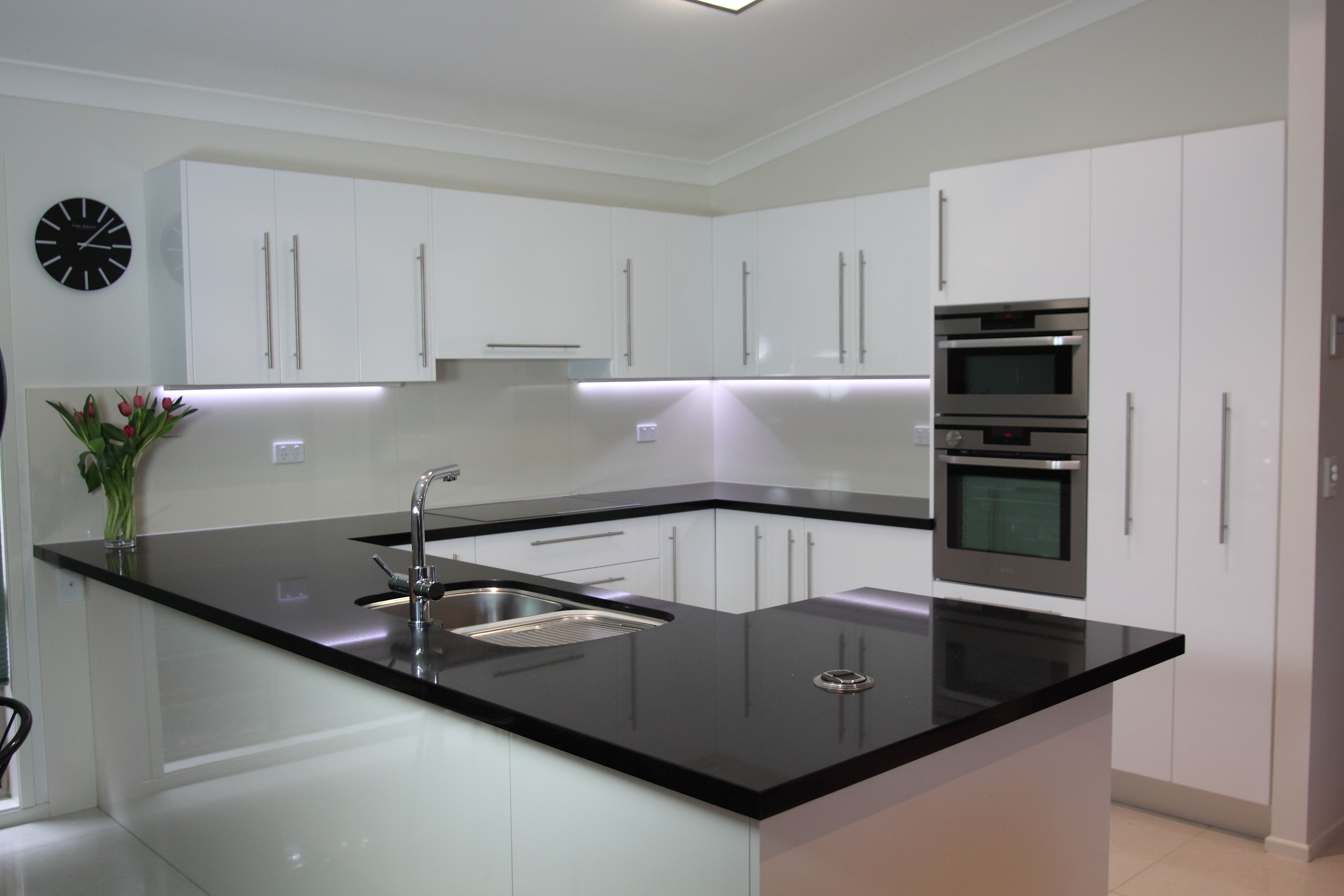 Black benchtop, white cupboards. Classic style that never