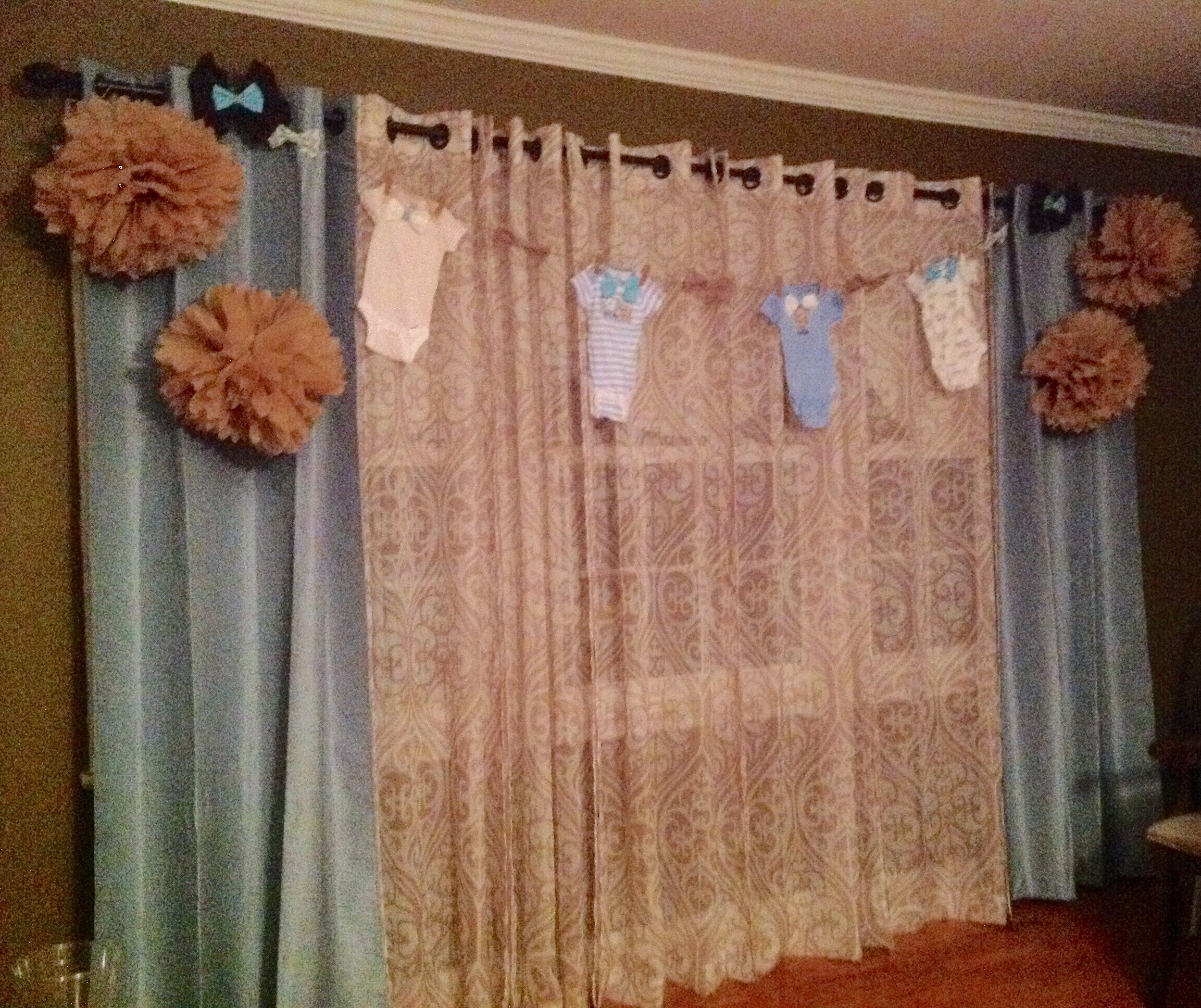 Baby shower, pompoms, banner onesies, tan and mint green.