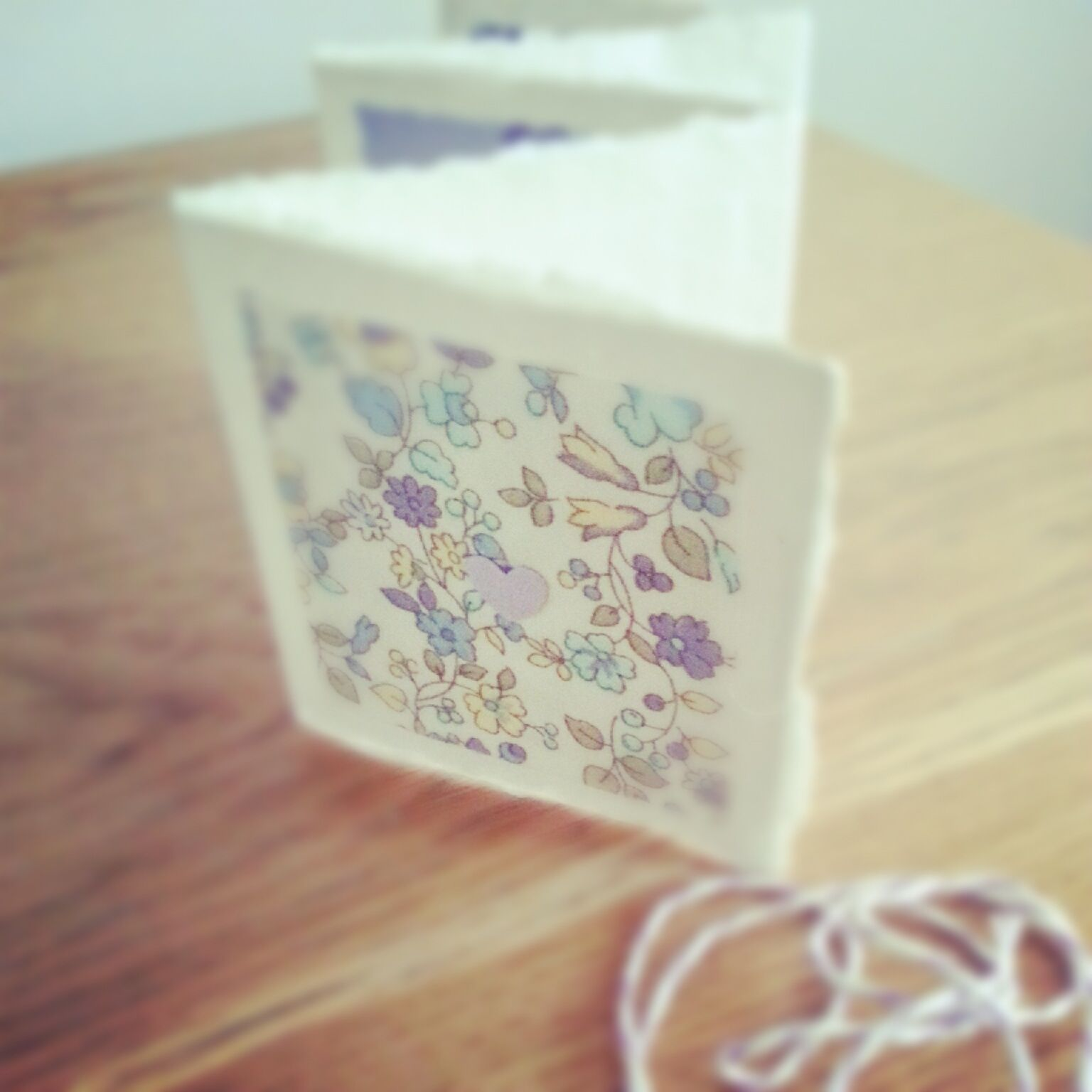 A zig zag pocket size invitation made from recycled rag paper and fabric squares - gorgeous!