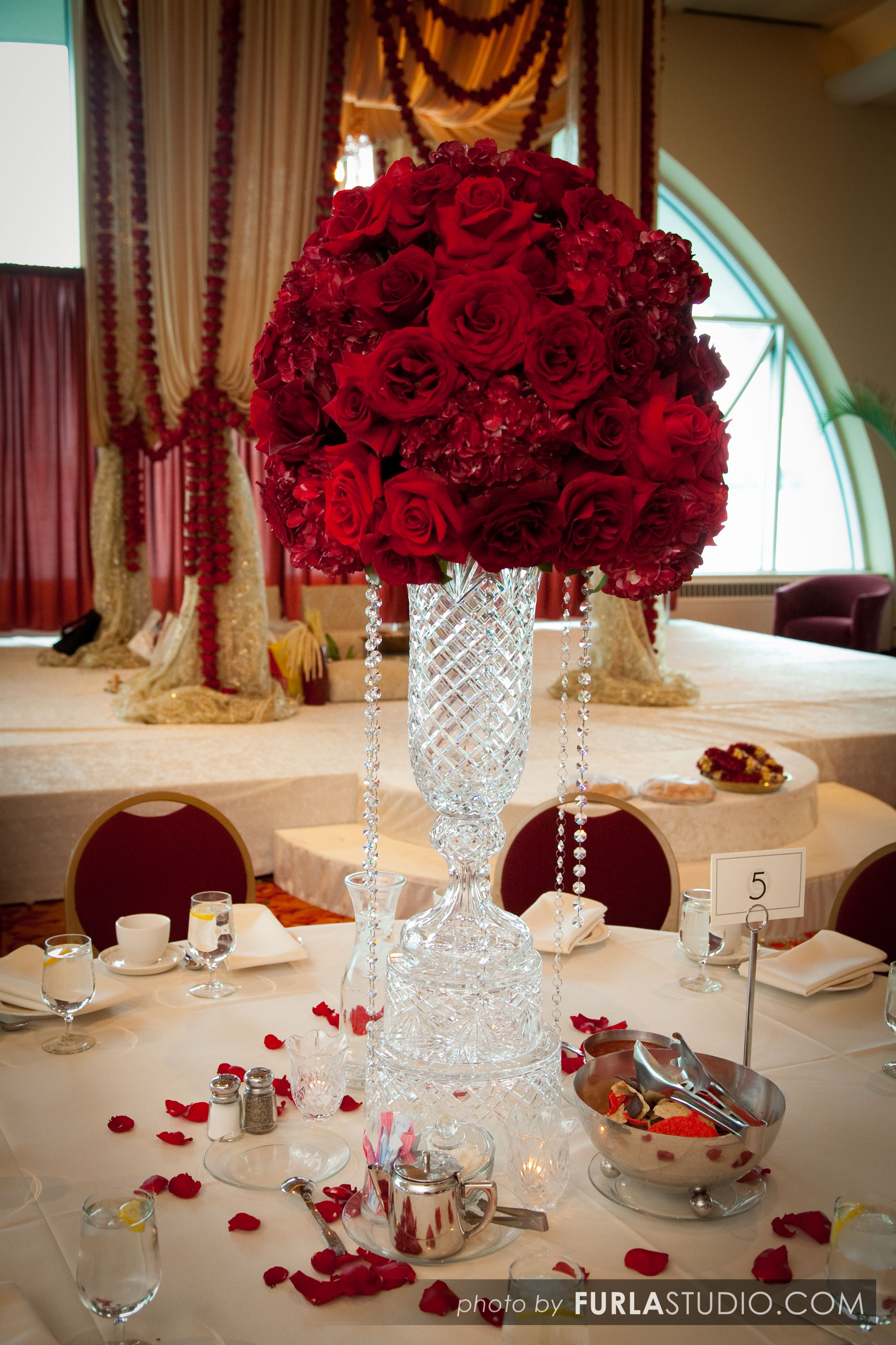 A Very Traditional Red Fl Centerpiece Atop Swarovski Crystal Vase And Dishes Accented With Hanging