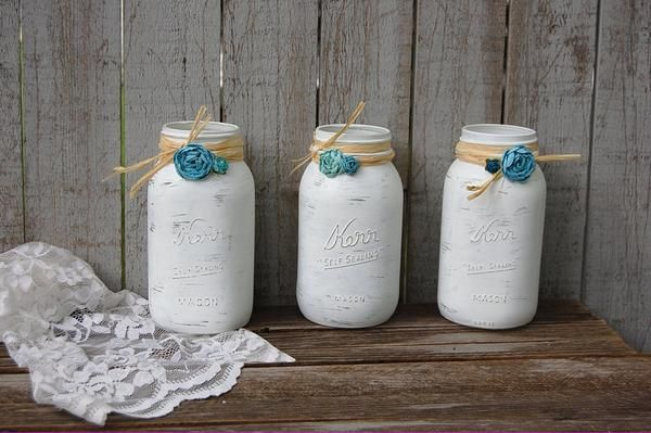 3 hand painted mason jars, done in white, lightly distressed, wrapped with a twist of raffia, papercraft flowers, and a protective coating. They are not painted
