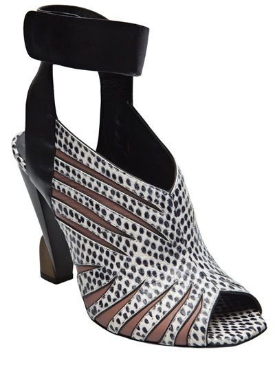 Heeled sandal from Balenciaga featuring a black and white animal print. These leather sandals feature an open toe, wrap around ankle strap with double button snap closure, brown underlayer cutouts on front, and sits on a 4
