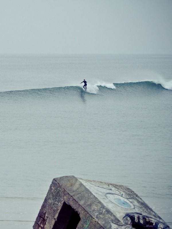 "surfsouthafrica: "" Thomas Lodin is one of the best up-an-coming surf photographers. Here he captures a lone surfer hanging five in Brittany, France. """