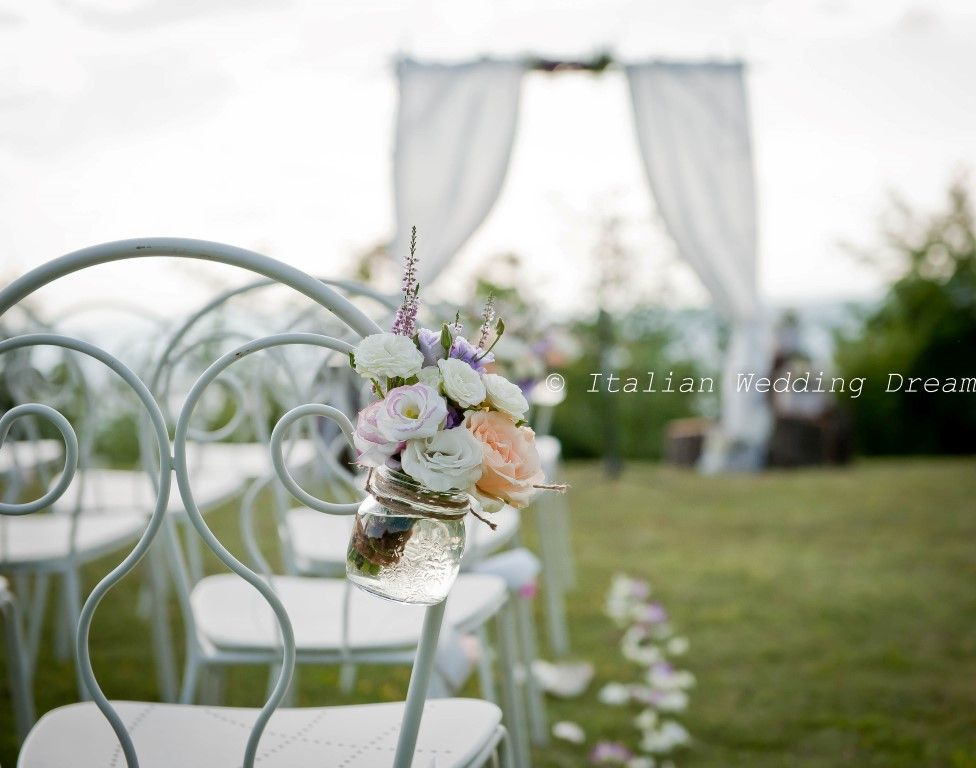 Ceremony chairs decorated with flowers in mason jars
