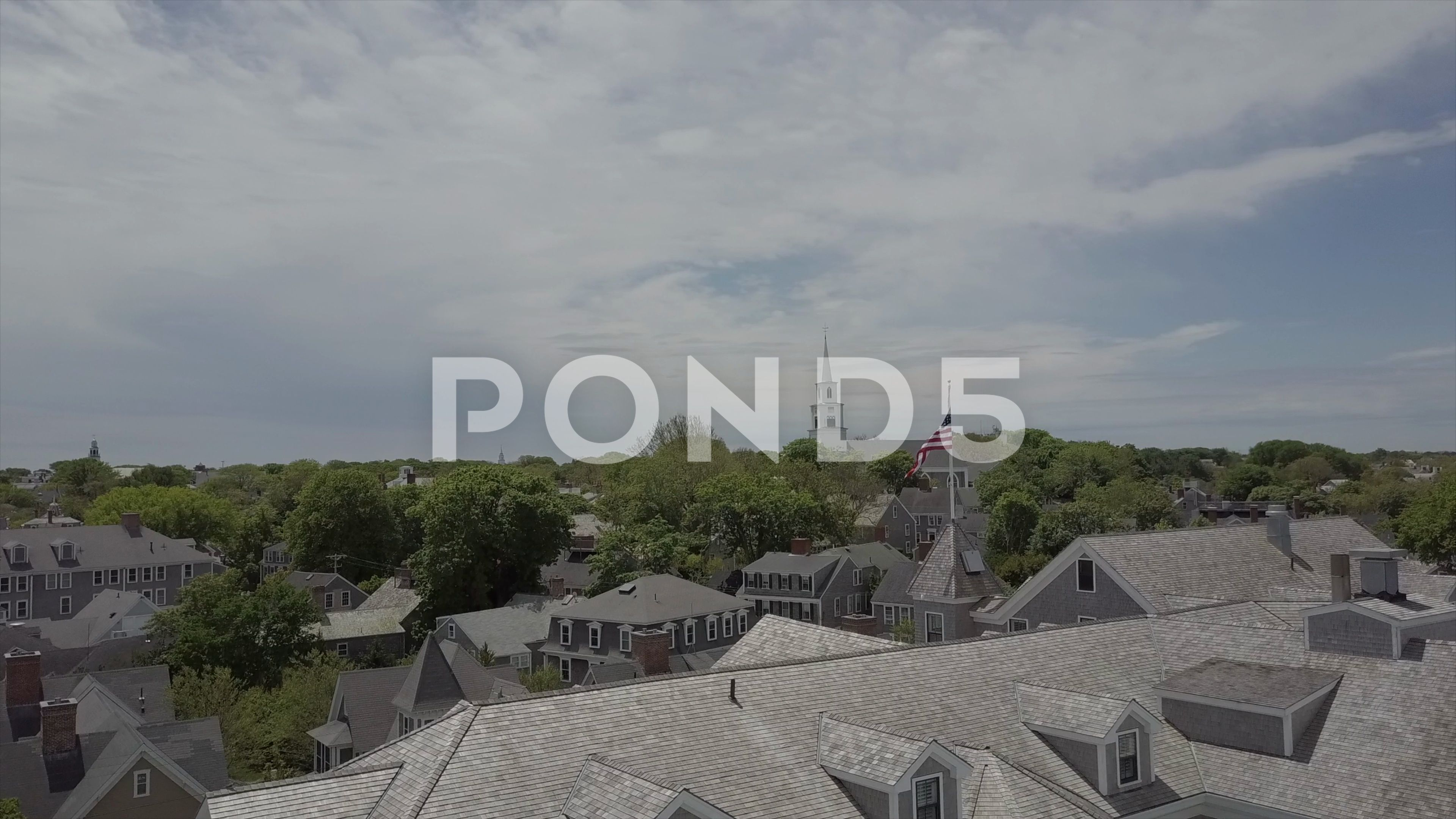 Aerial Drone Footage Of Coastal Town With American Flag Waving Stock