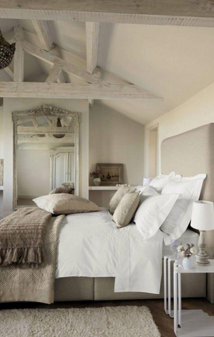 Slapen onder het dak. Een schuin dak en balken geven de slaapkamer ...