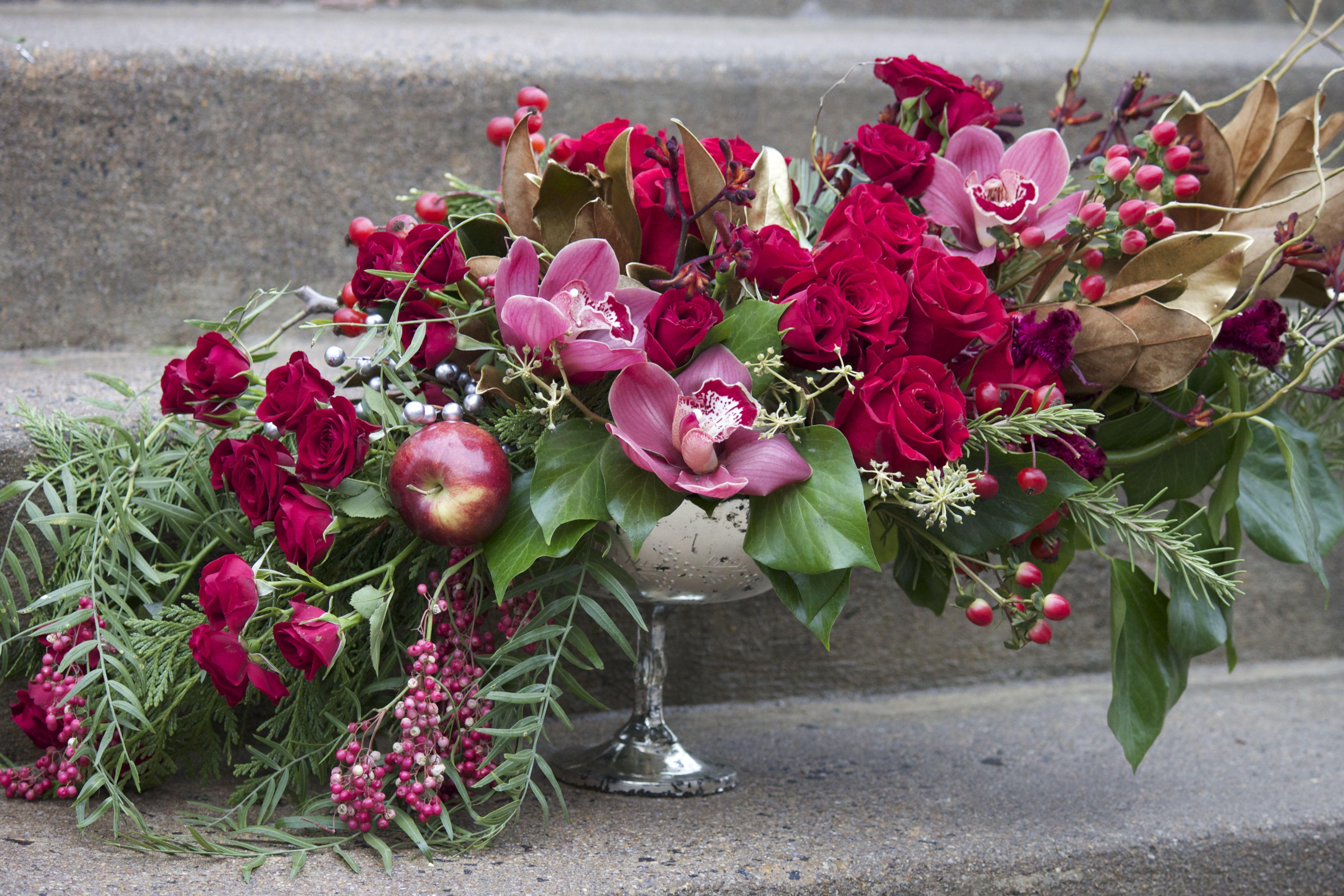 Avant-garde design, red roses, red Cymbidium orchids, apples, pepper-berry, spray roses, Hypericum berries, gold Magnolia leaves, rose hips, curly willow, bush ivy, cedar - mercury glass pedestal vase. Design by J. Morris Flowers