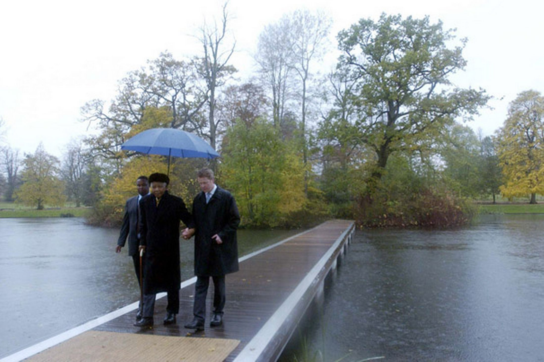 Remembering Diana: Mandela and Earl Spencer walk, across a pontoon from the island where Diana, Princess of Wales, is buried