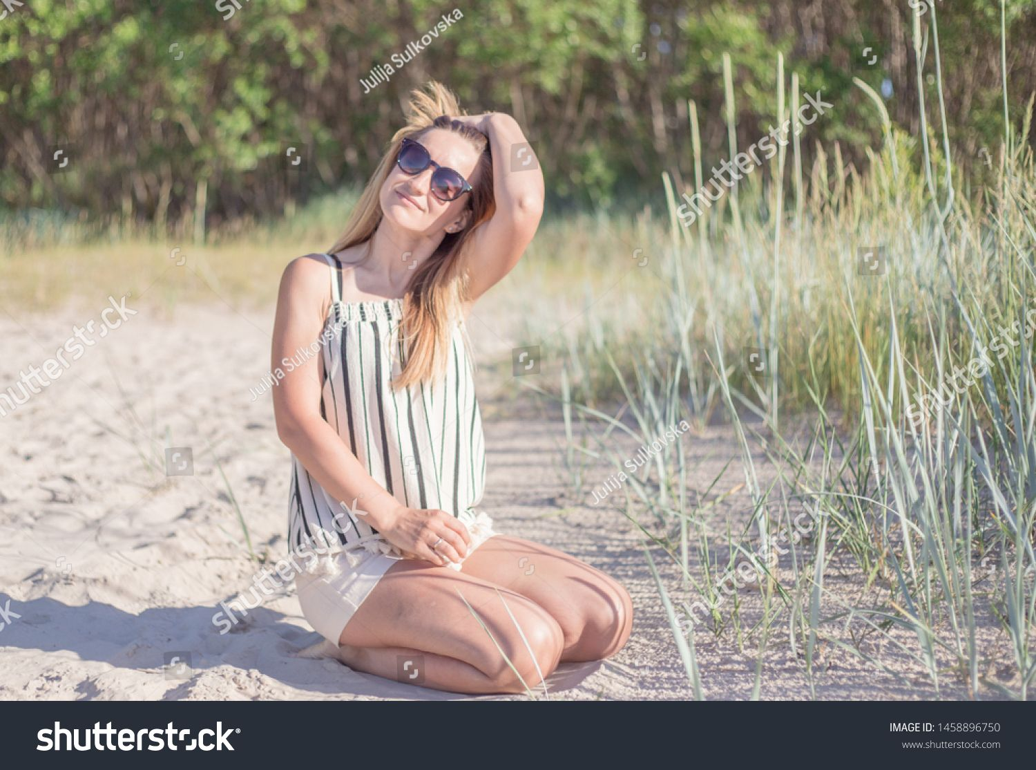 Portrait of beautiful young woman posing on the beach. Female fashion model posing atthe coast.Stylish woman at the summer beach in a hot day. #Sponsored , #AD, #posing#beach#Female#woman