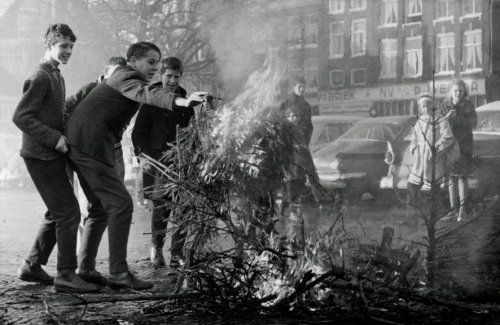 Kerstboomverbranding in Amsterdam. Vier jongens bij een brandende kerstboom. Twee meisjes kijken toe op veilige afstand. Amsterdam, 2 januari 1962.