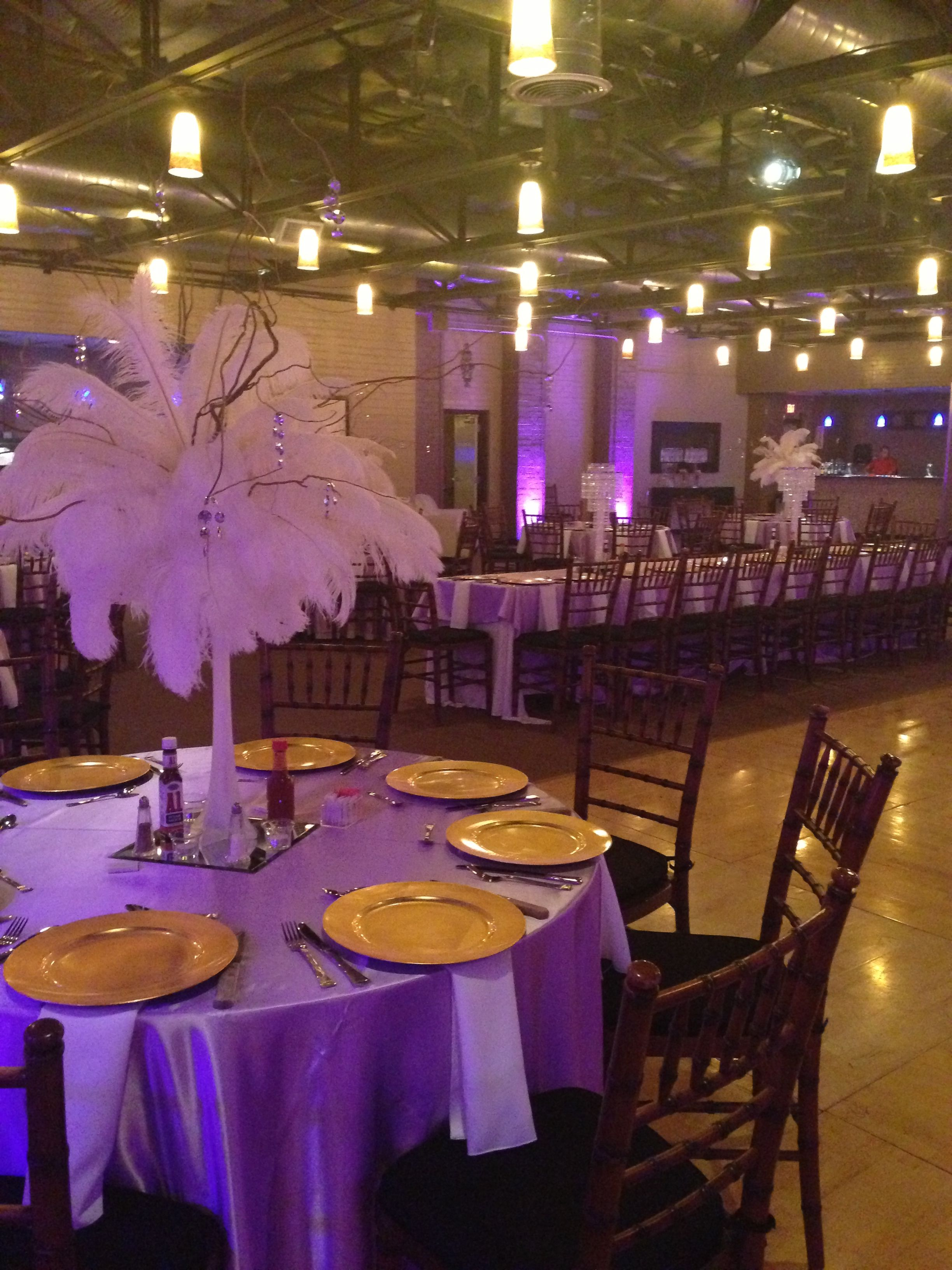 purple uplighting and feather and curly willow centerpieces Also