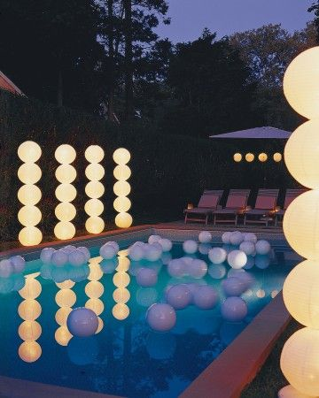 """Light Columns - Geometric """"topiaries"""" inspired by the paper sculptures of Isamu Noguchi stand on both sides of this swimming pool. A few white plastic beach balls tied to weighted lines float in the pool like pearls cut loose from a giant strand (for safety, never cover the surface of a pool with a large number of balls)."""