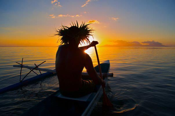 Tahitian man in outrigger canoe at sunset