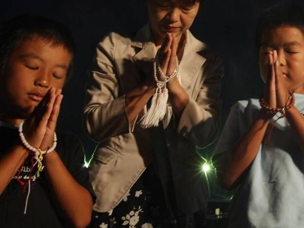 6 August 2013: A mother and her children pray for atomic bomb victims of Hiroshima and Nagasaki