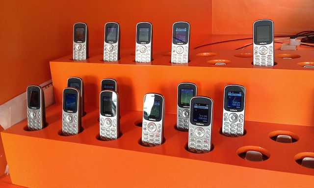 """""""Can you hear me calling...,"""" by Librarian In Black, via Flickr -- """"A stable of cell phones [at DOK, Delft]. Employees grab one on arrival and log in, connecting that phone to their accounts. Clocks them in and out and routes calls to them wherever they are."""""""