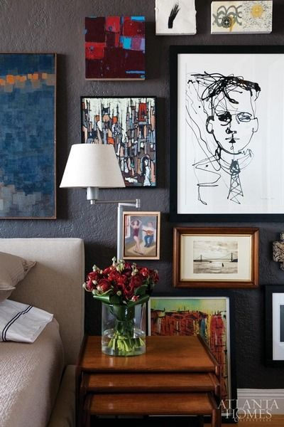 Art gallery wall in the bedroom! Dark slate wall doesn't compete with the colors in the art. Love !  Via Zsa Zsa Bellagio