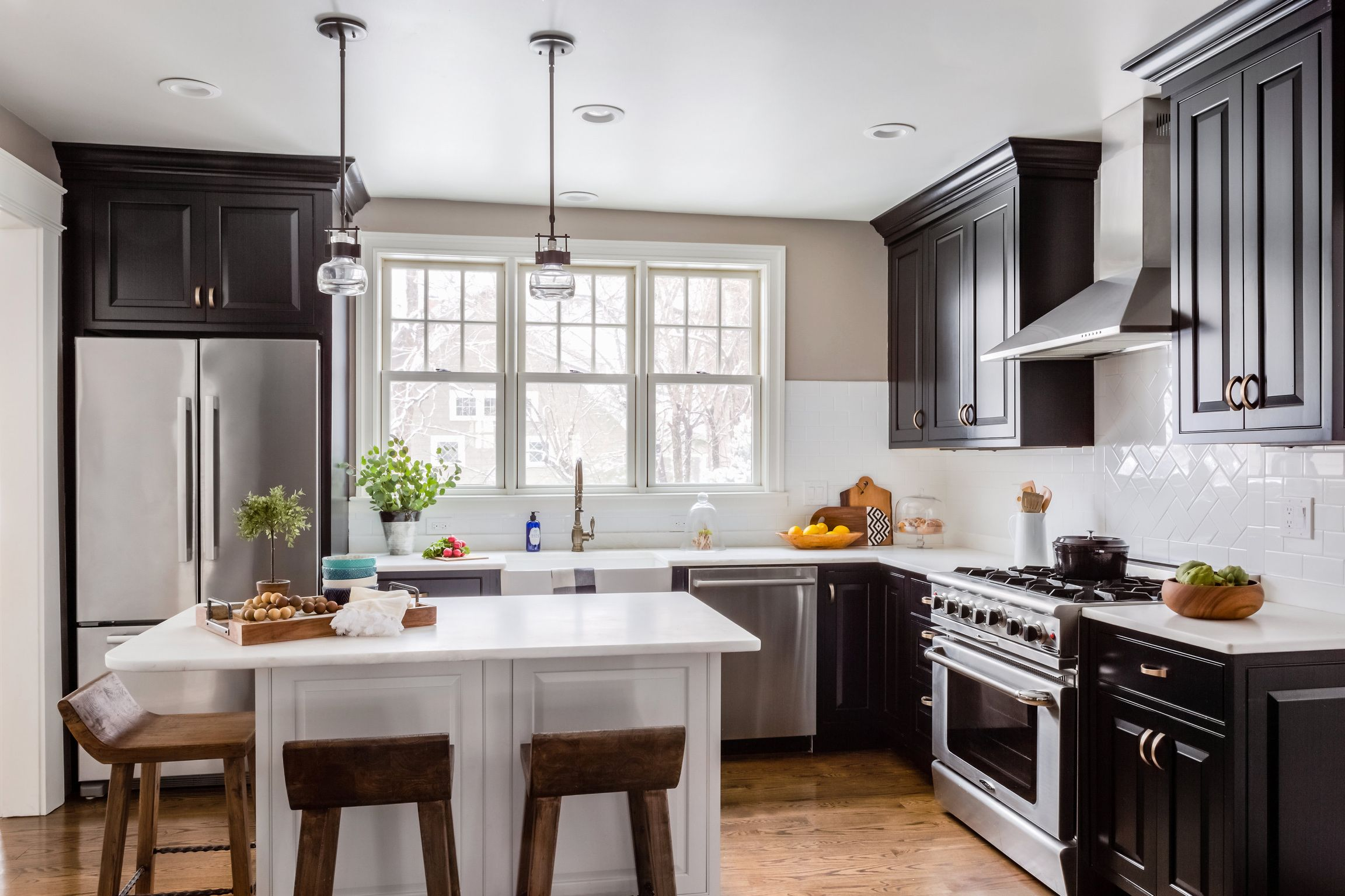 Black cabinet kitchen with white marble countertops make up this ...