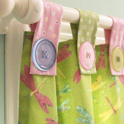 Cortina com ilhós de tecido e botões coloridos.