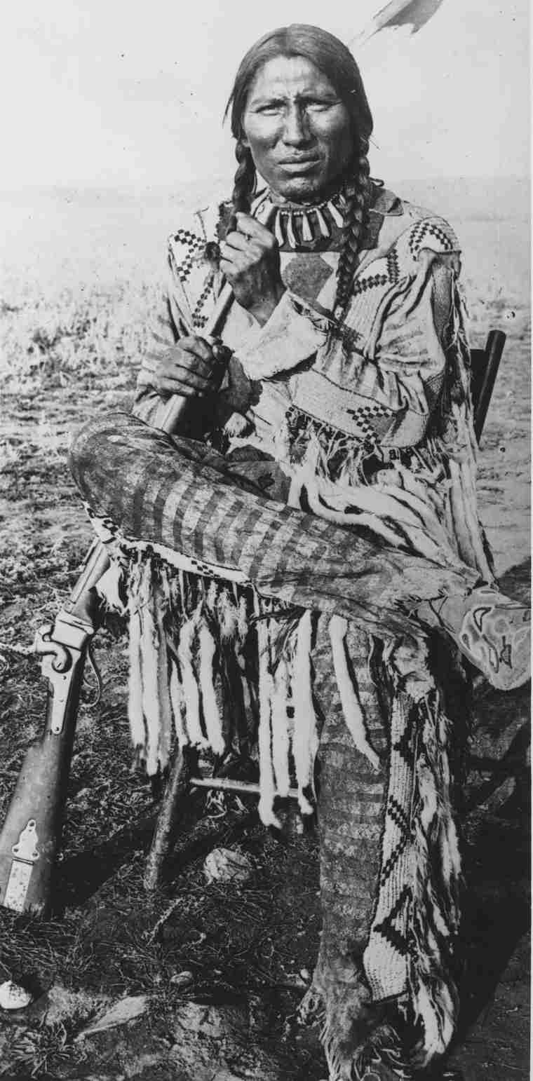 Our Legacy| Peigan Chief Bull Plume with rifle sitting on a chair on open prairie. Wearing traditional clothes.