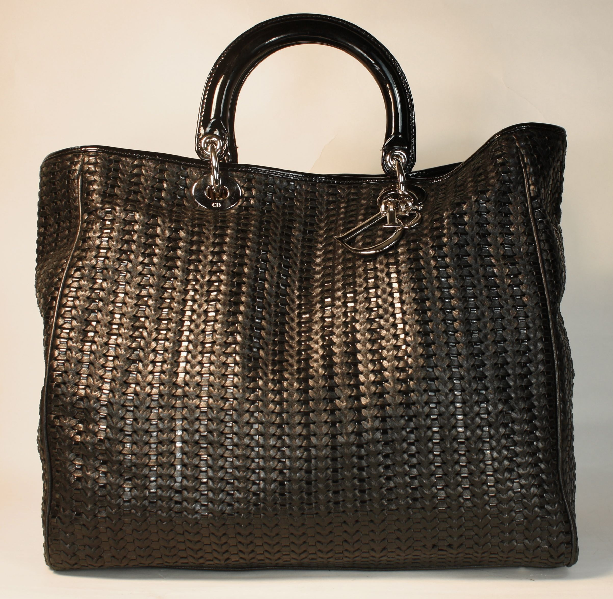 Christian Dior Tote Bag is done in woven black leather. The hardware is  done in silver. The black patent leather handle boast a 4 inch handle drop. 3f3afdcbe11e5