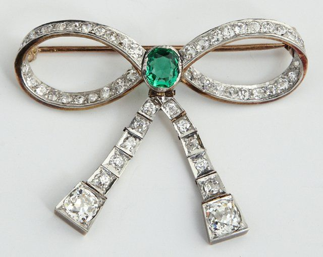 Edwardian Platinum, Diamond and Emerald Brooch, c. 1910, of bow form, featuring a central oval brilliant cut emerald, app .6 cts., accented by 52 old European cut diamonds on the bow, app. 3.3 cts., in platinum over 18K rose gold . Provenance: Estate of Rose Finegold, New Orleans, LA. H- 1.75 in., W- 1.75 in.