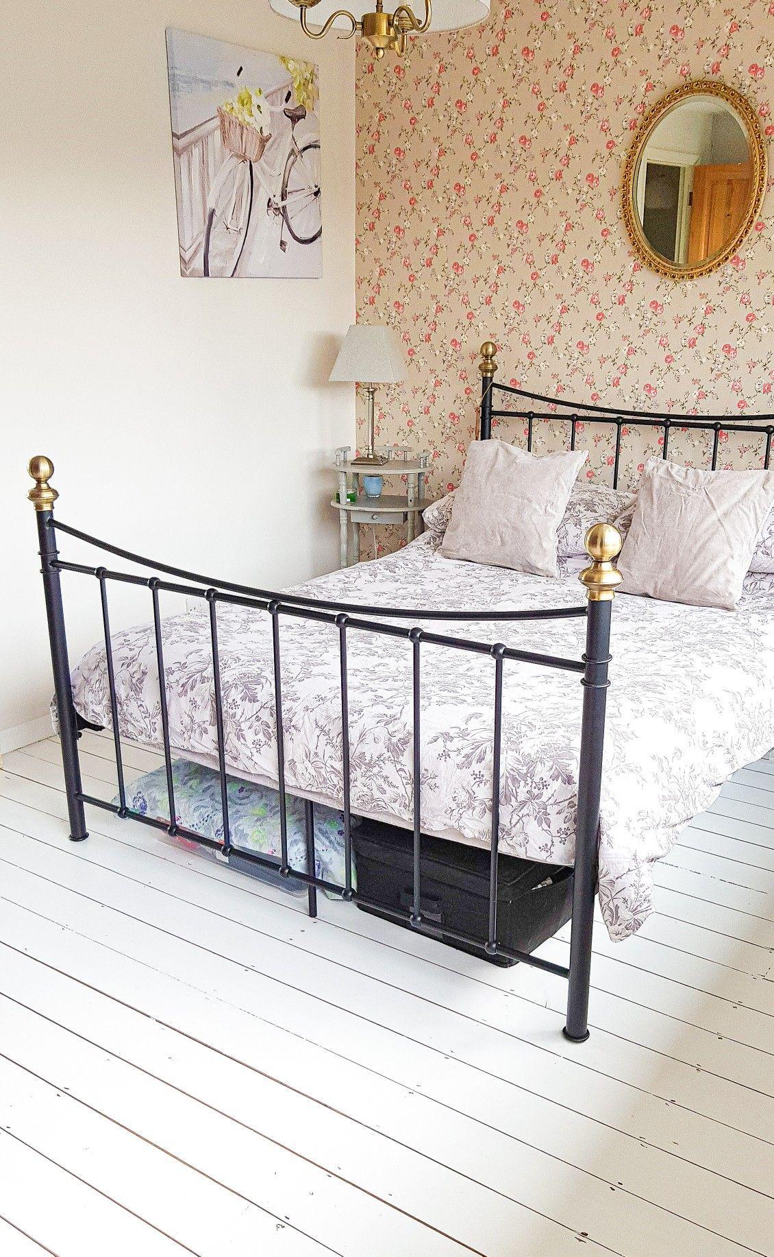 White washed floorboards in bedroom. Floral wallpaper