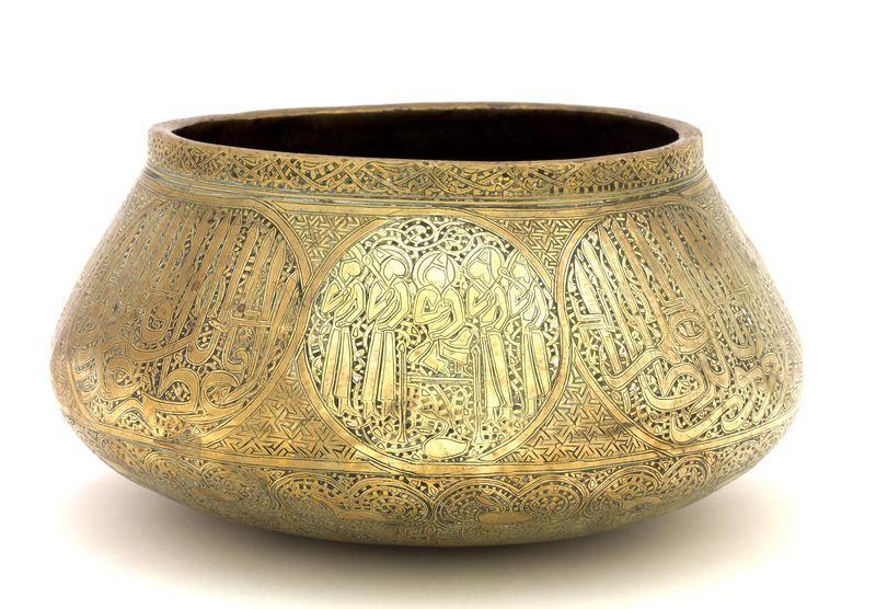 TAS BASSIN PERSAN DU XIVe SIÈCLE en cuivre ciselé en champlevé autrefois incrusté d'argent et de pâte noire, décoré de quatre rondeaux ornés d'un notable trônant entouré de quatre courtisans debout, alternant avec quatre cartouches épigraphiques en thuluth à longues hampes, doublé en coufique : El-'ezz limawlâna-s-sultân al-a'zam mâlek ruqâb al-umam al-salâtîn al-'arab al-'ajam al-'âlem al- 'âlem ...