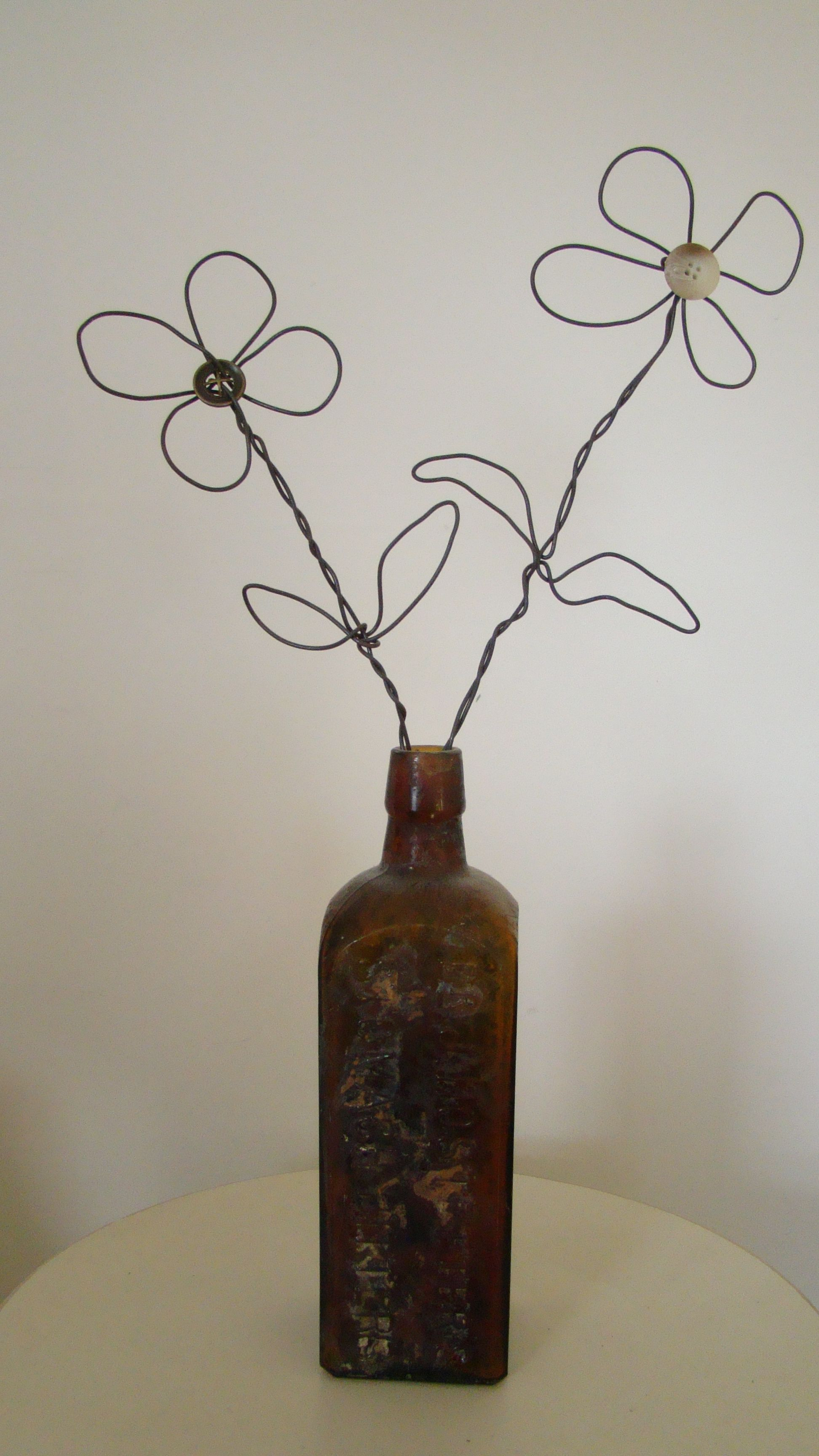 old bottle with wire and button flowers