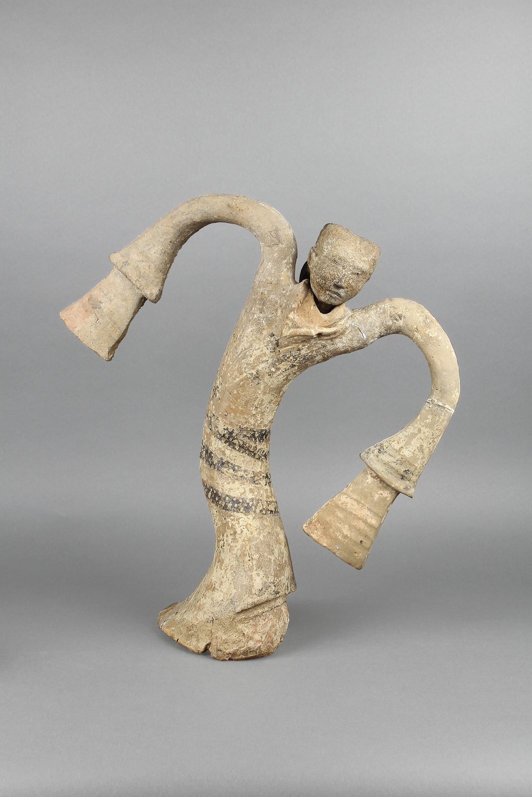 """With her dramatic posture and outstretched arms, the bold design of this figurine captures a dynamic and graceful moment of the """"flying swallow"""" dance. Possibly belonging to the third king of the Chu kingdom, the Tuolan Mountain tomb housed an ensemble of these dancing figurines, allowing us to imagine the spectacle of courtly entertainment."""