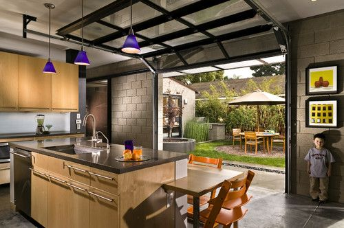 Modern Glass Garage Doors Open Up The Kitchen To An Outdoor Courtyard Neat Idea Garage Door Design Modern