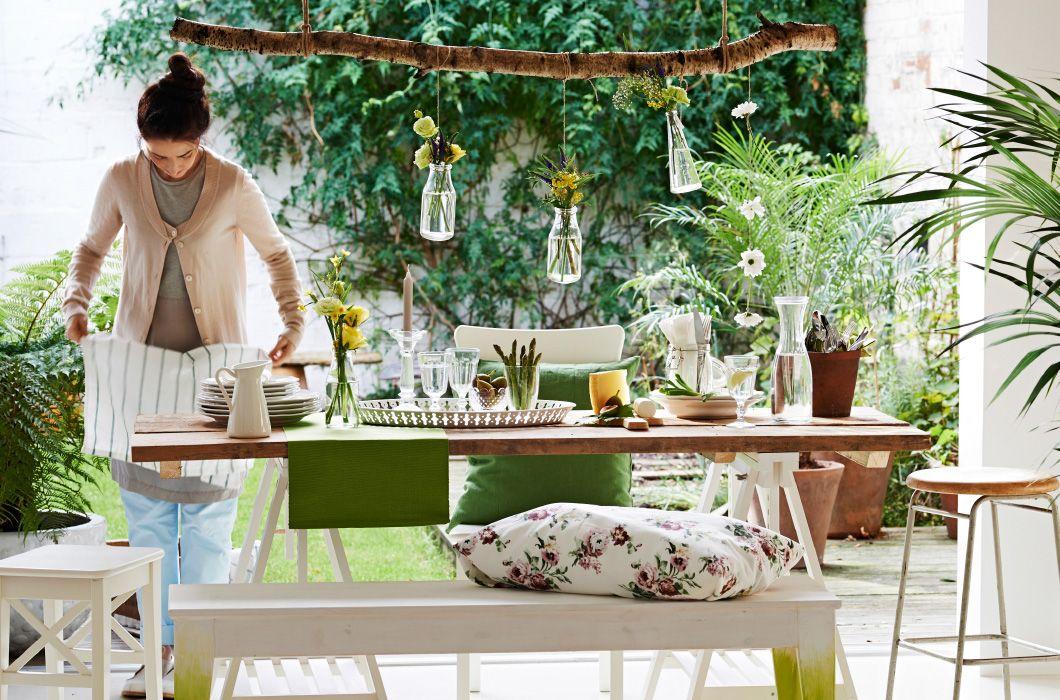 Billede af uformelt dækket træbord med planter og grønt tilbehør. NORNÄS bænk af træ gjort personlig med puder med botaniske tryk.