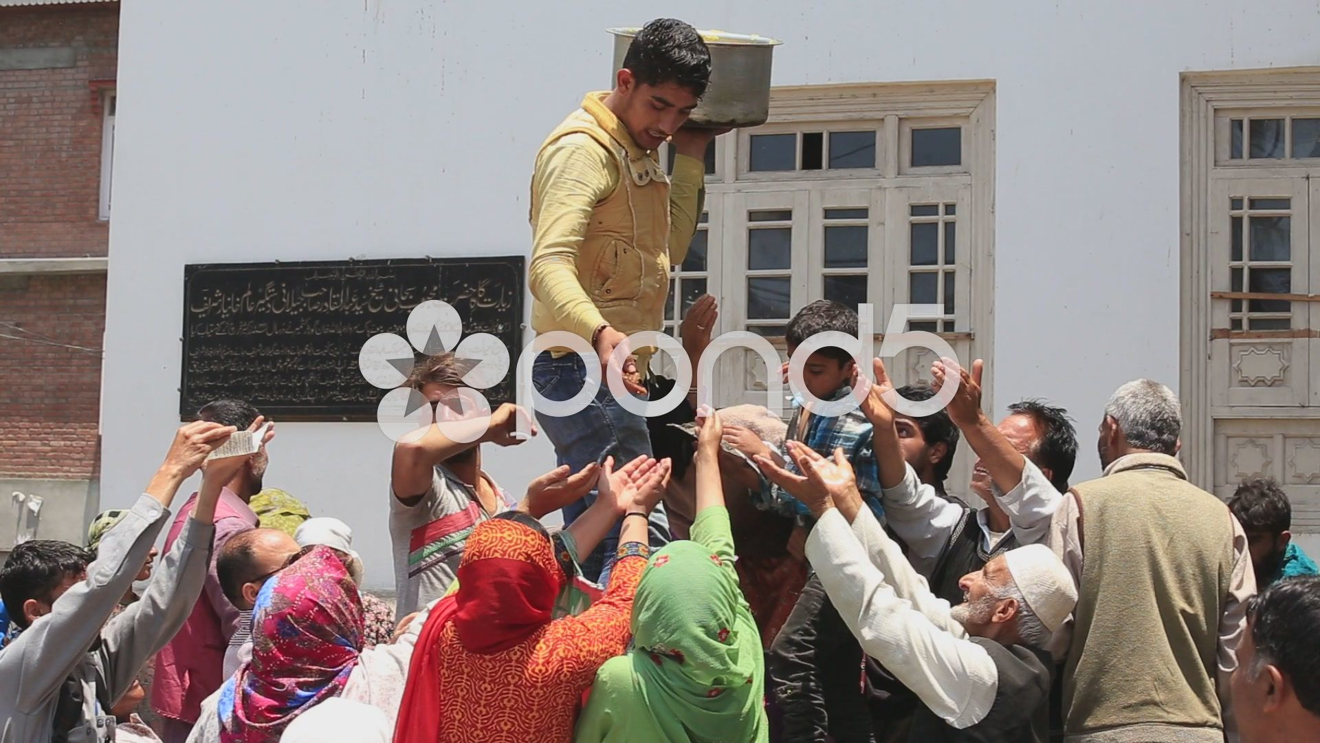 Indian man feeds the hungry people near a muslim mosque