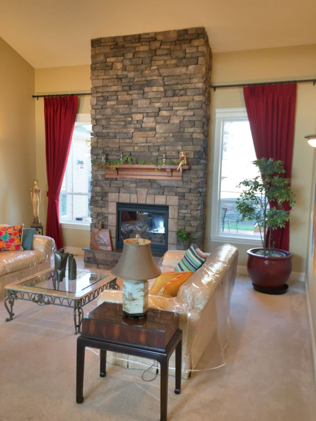 Custom Red Drapery In A Living Room Featuring A Brick Fireplac
