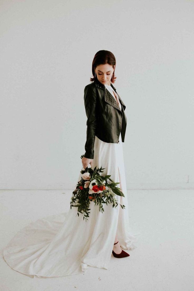 Offbeat bride wearing leather jacket over wedding dress  Edgy Meets