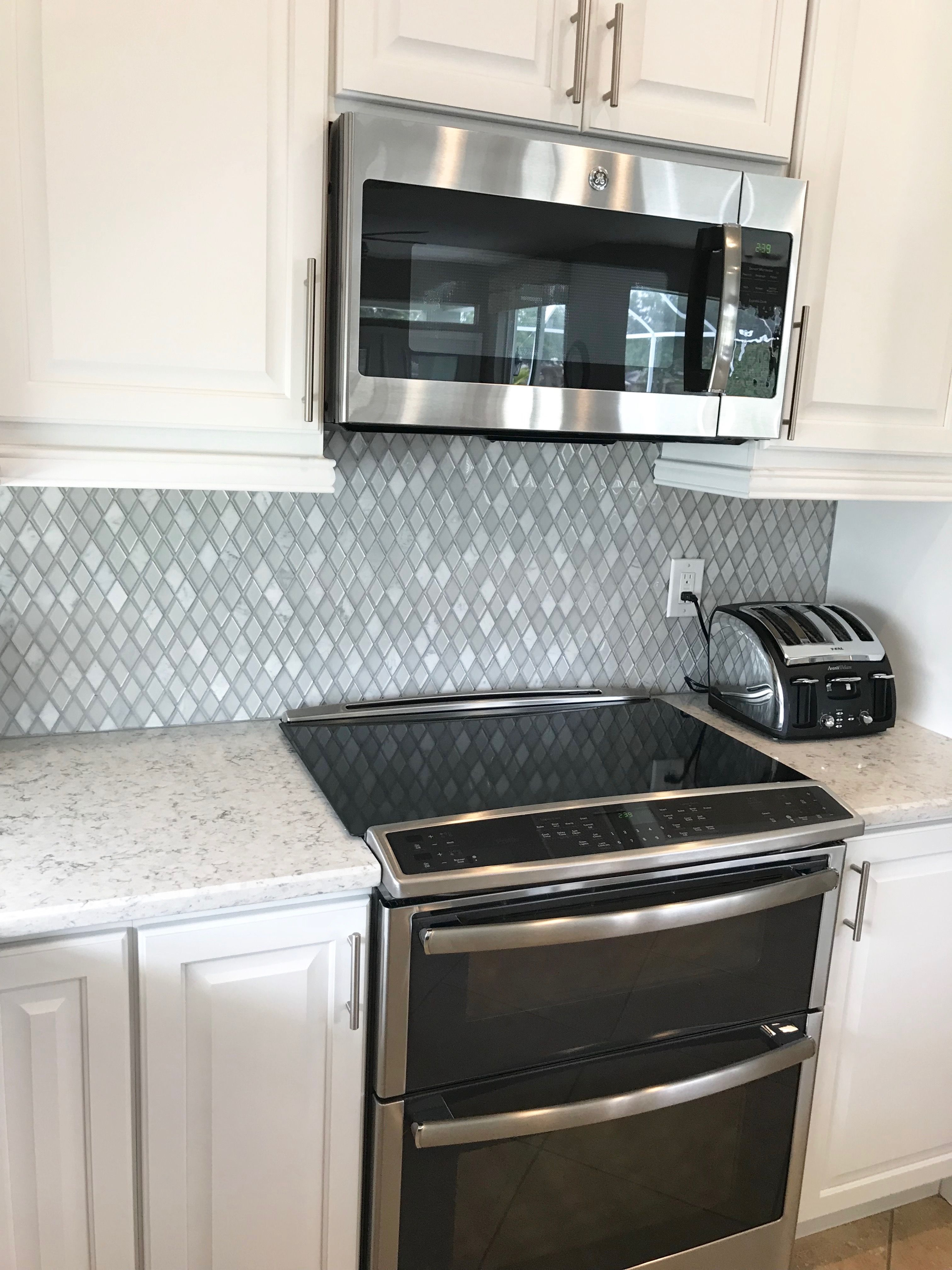 White Quartz Counter And Cabinets With Diamond Tile Marble Backsplash