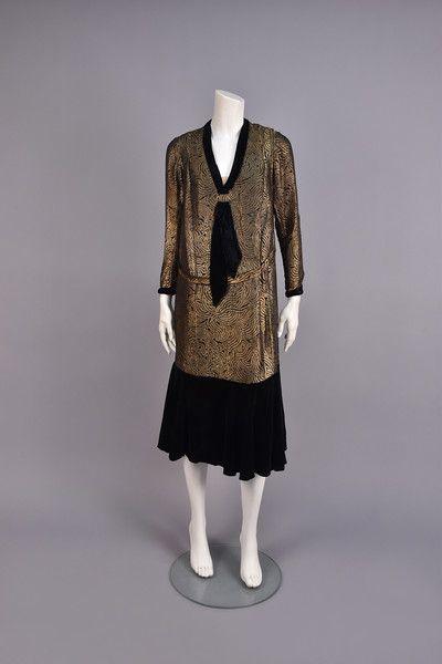 VELVET and GOLD LAME DINNER DRESS, 1920s. Black with foliate pattern in gold lamé, having long sleeve and V-neck with velvet tie, self belt, ruffled velvet lower skirt with side slit. - whitakerauction