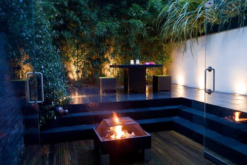A screen of black bamboo uplit at night Inspiring Homes and