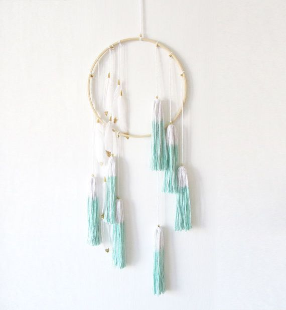 This boho-inspired tassel and feather dream catcher features seven hanging tassels dip-dyed in a teal/turquoise hue. Small flecks of shiny gold beads and hanging white feathers dipped in gold, give th
