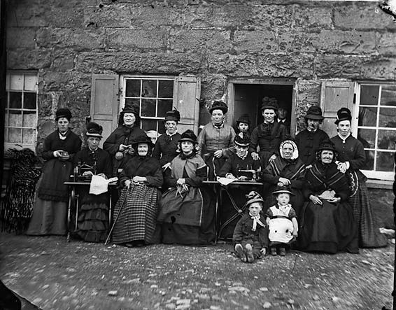 A group of Welsh Victorian women and girls of all ages posing outside with a pair of sewing machines. #Victorian #women #children #1800s #dress