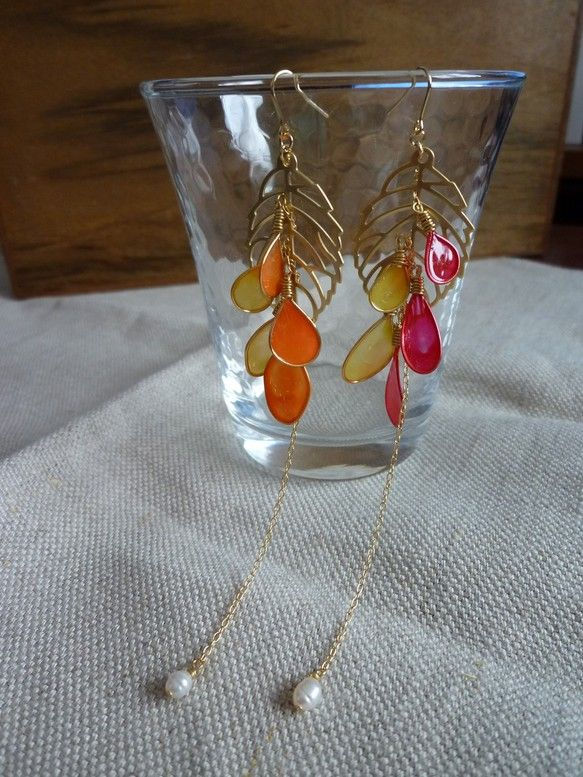 ゴールドの葉っぱにチェーンでアメリカンフラワーを連ねました。片方は黄色とオレンジの花びら、もう片方は黄色と赤の花びら。一粒、淡水パールが下がっています。【素材...|ハンドメイド、手作り、手仕事品の通販・販売・購入ならCreema。