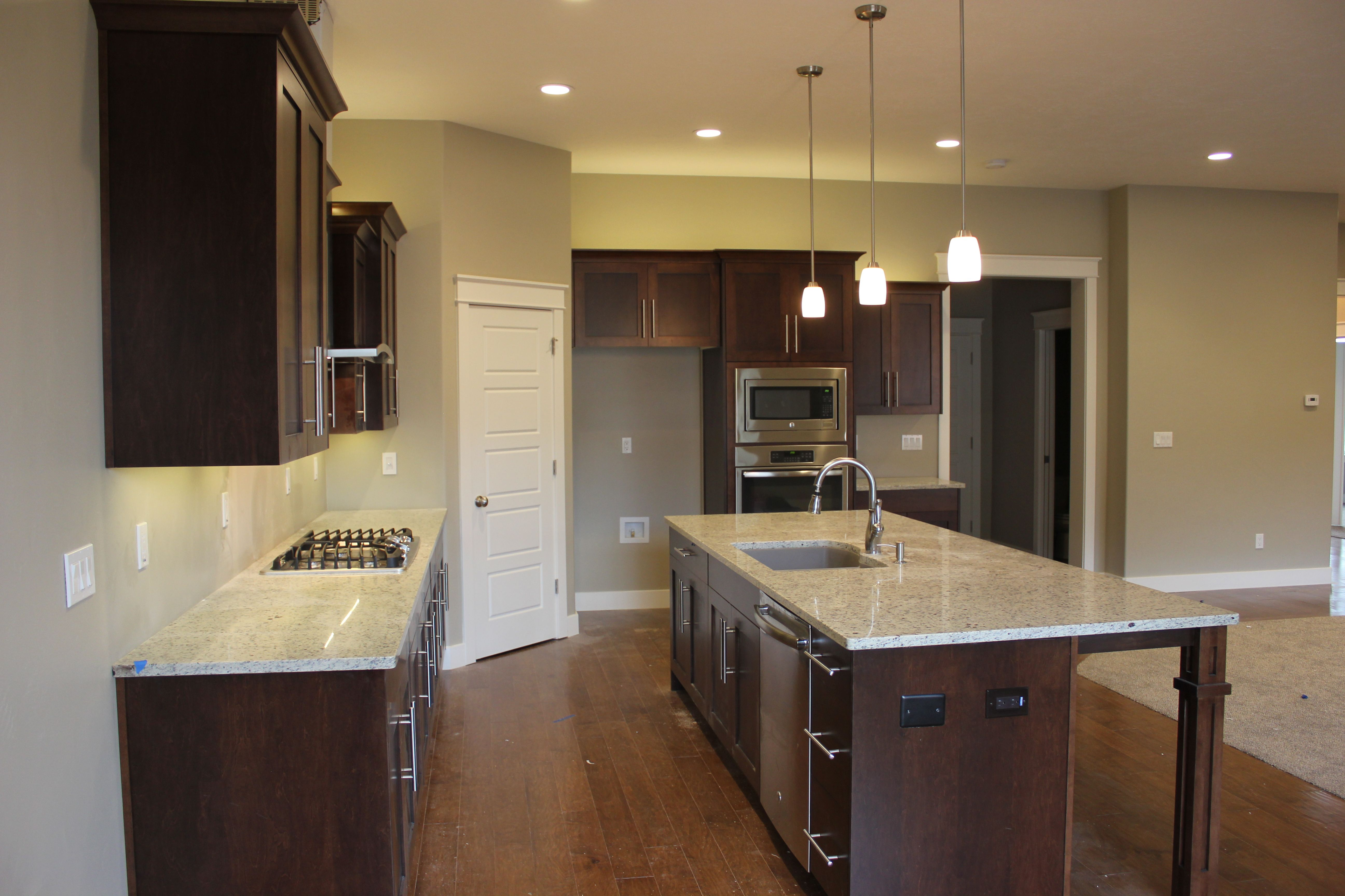 Dark maple cabinets with a light granite countertop ... on Maple Cabinets With Black Countertops  id=61081