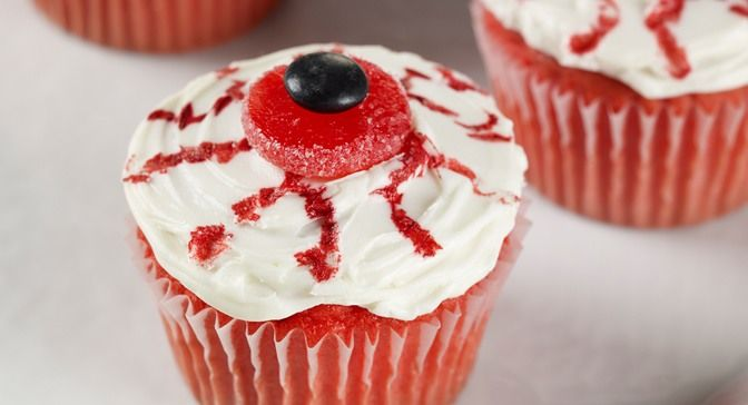 """Screams of delights will accompany these eye-catching cupcakes. Drag a toothpick dipped in red food color along the white frosting to draw the """"bloodshot"""" lines."""