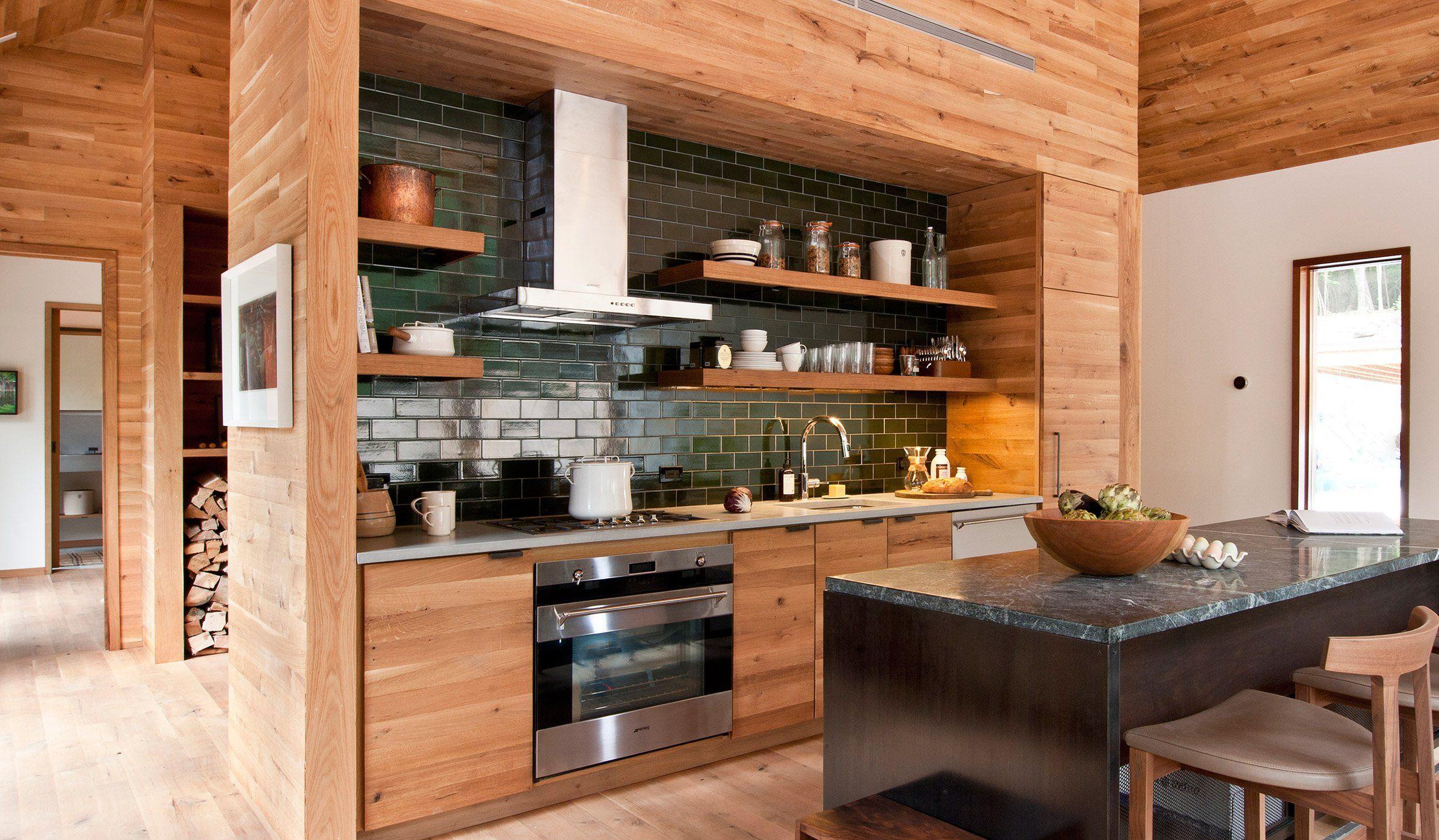 Apaixonante esta #cozinha aberta, toda em #madeira – revestimento que se estende pelo teto e algumas paredes da casa. O detalhe da #cerâmica verde atrás da bancada é a cereja do bolo!