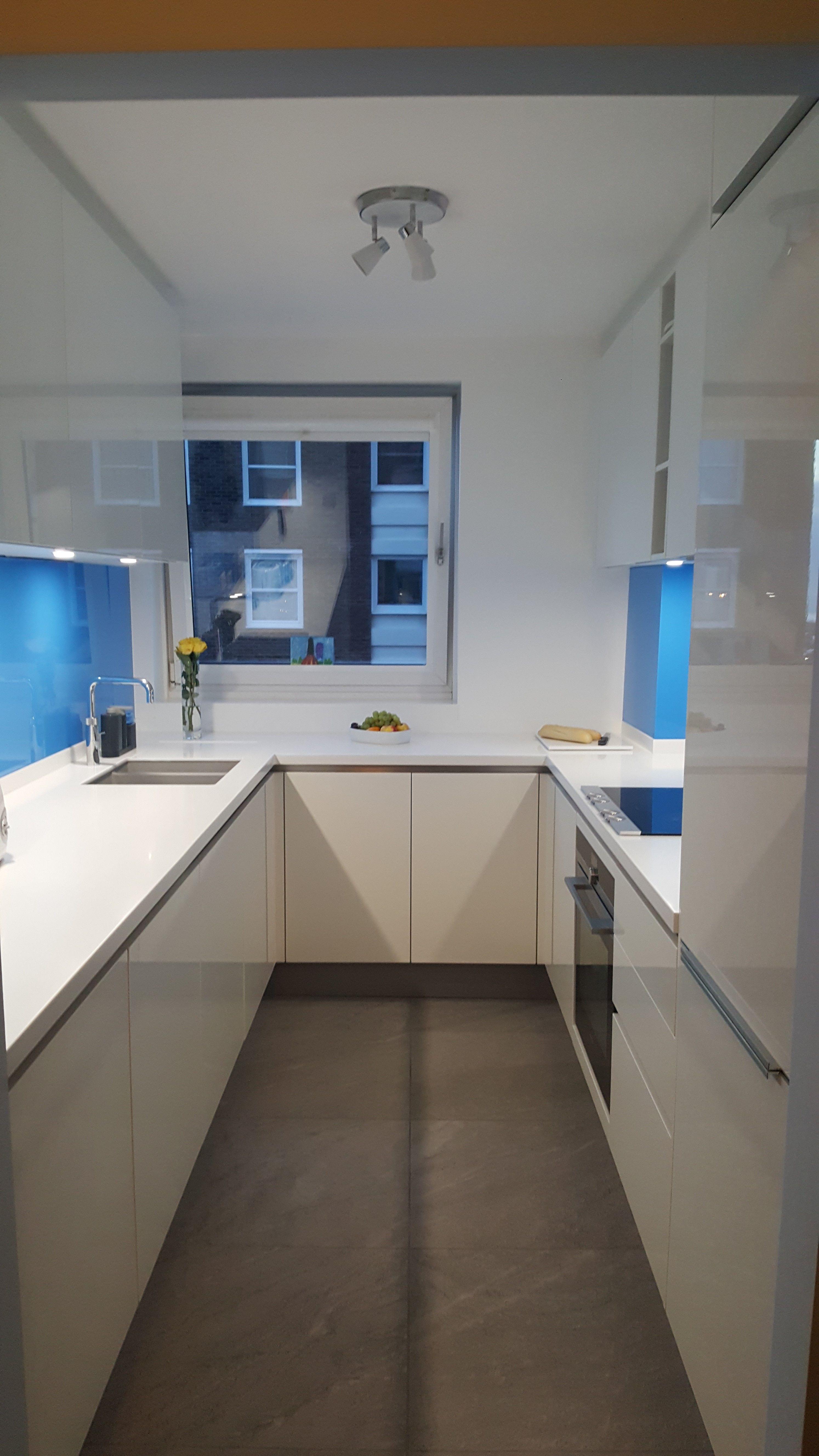 A Striking White On Kitchen With Vibrant Blue Gl Splashback Finished Glacier Corian Worktops German Kitchens Dupont