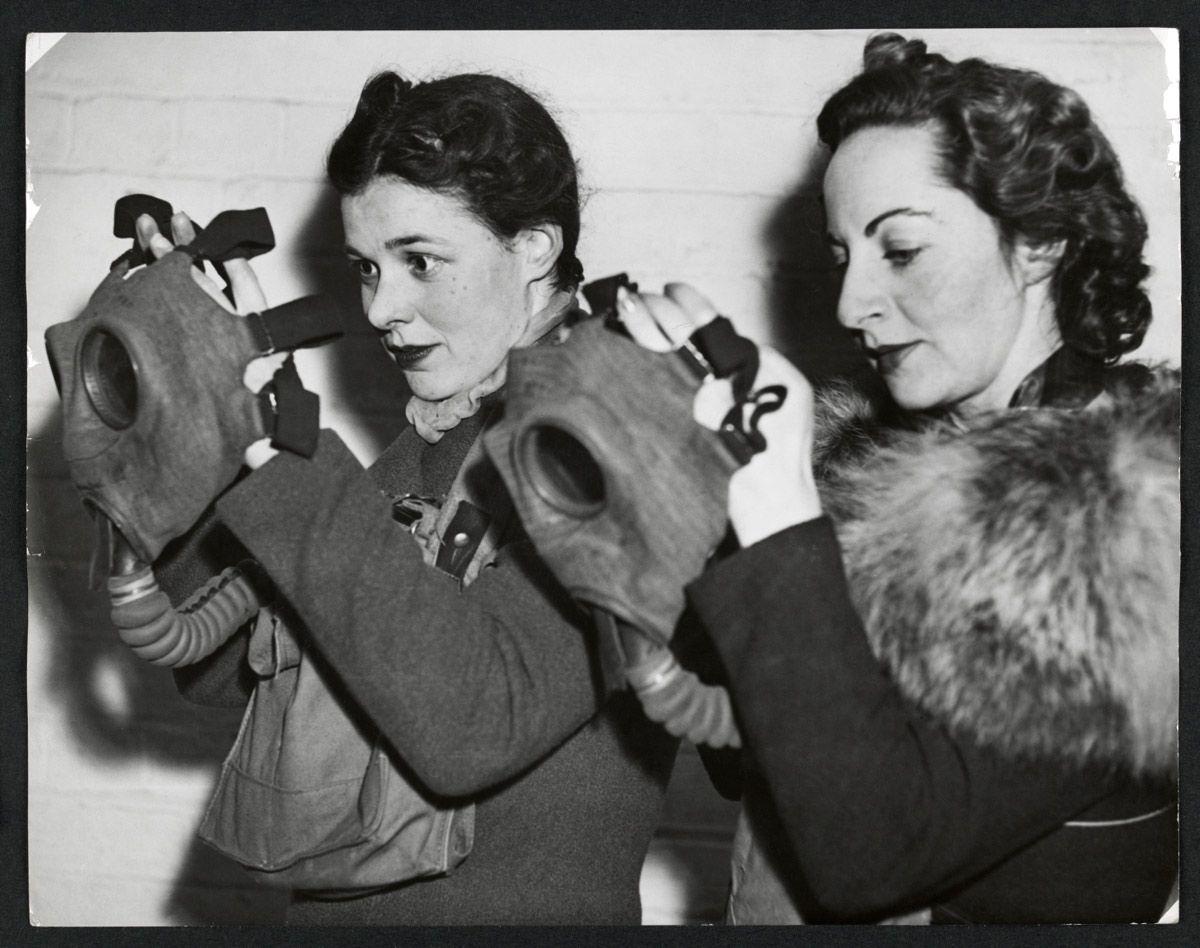 'Two women donning gas masks as part of an air raid drill