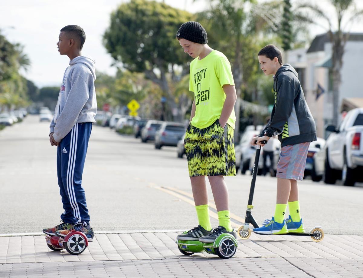Tre bambini di cui uno afroamericano vengono ripresi mentre si spostano in città con degli hoverboard e un monopattino