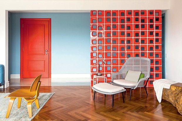 Nos 50 m² de sala deste apartamento, o certeiro contraste do azul com o vermelho é o que dá personalidade ao espaço. Idealizado pela equipe do escritório Patrícia Martinez Arquitetura, o ambiente recebeu, como contraponto ao tomdo corredor, uma divisória de elementos vazados Quadratto, da Elemento V.
