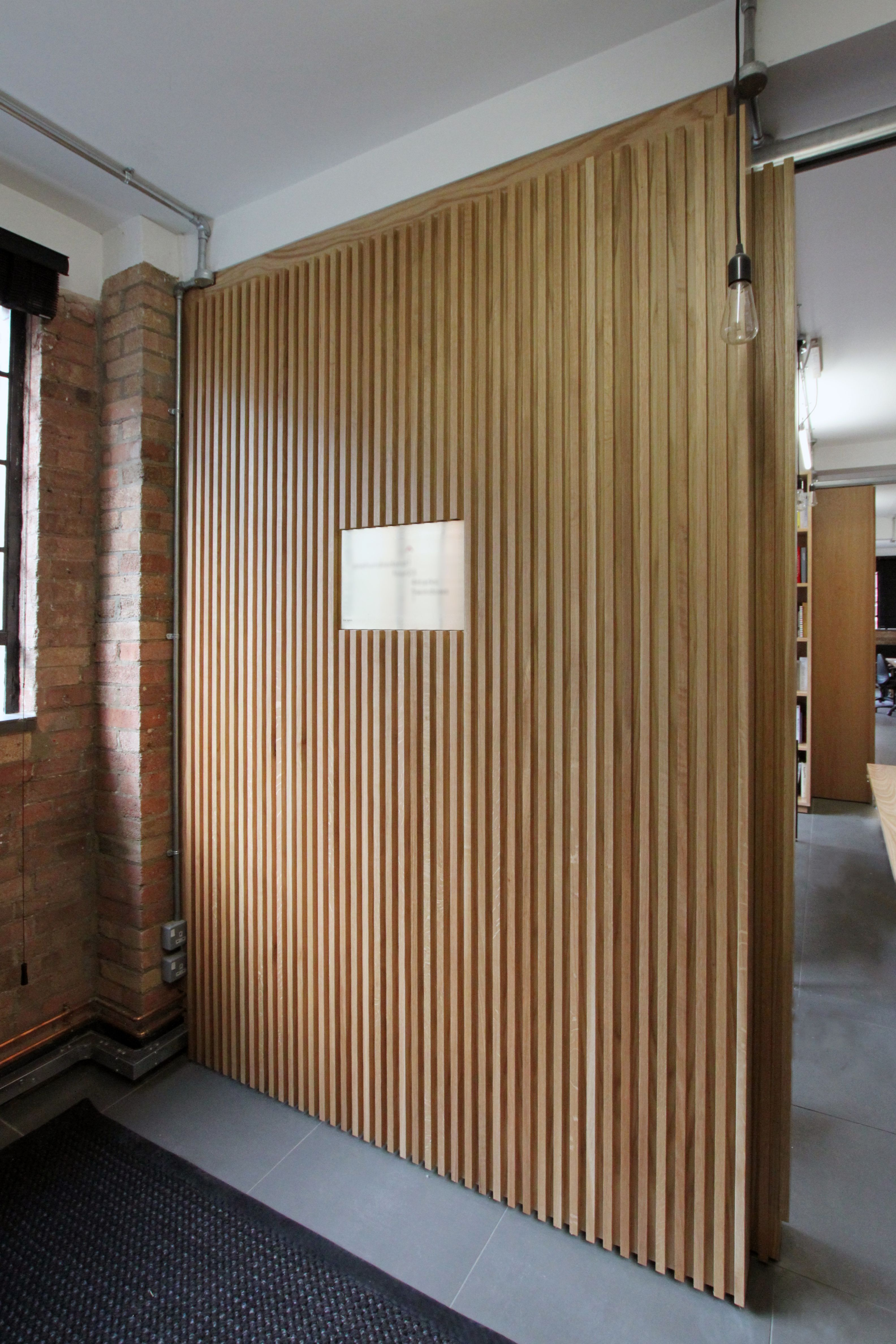 Floor to ceiling oak veneer room dividers with partition for House of tracks